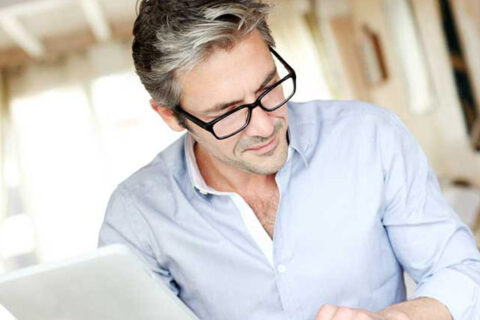 Man holding tablet and book